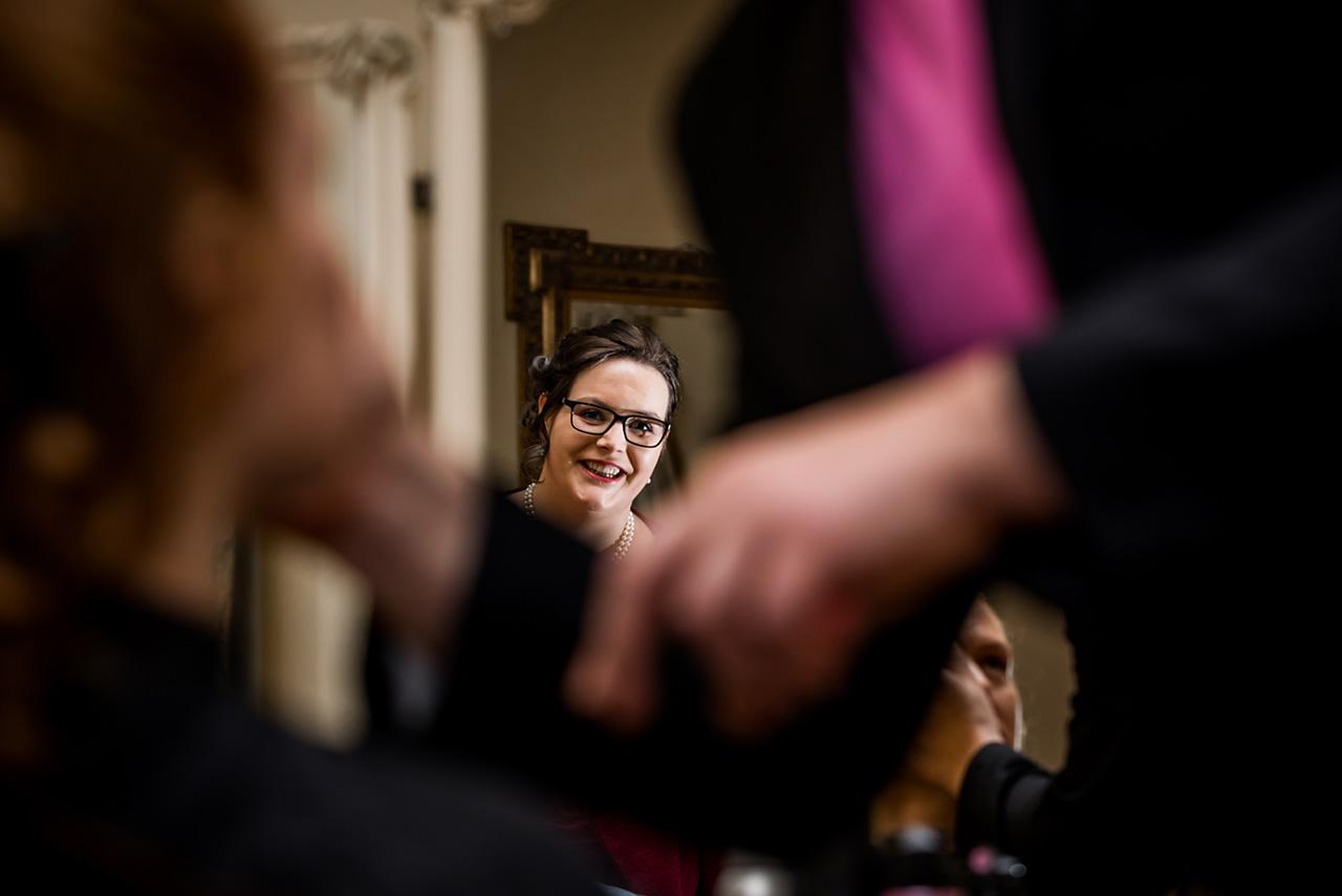 Freundin schaut beim Schminken der Braut zu und lächelt - Hochzeitsfotograf