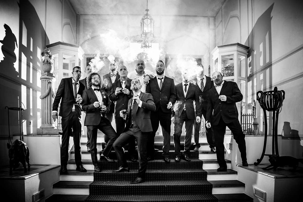 Gruppenfoto Bräutigam steht cool mit seinen besten Freunden auf Treppe im Eingangsbereich Schloss Bredenfelde und alle rauchen - Hochzeitsfotograf Bredenfelde