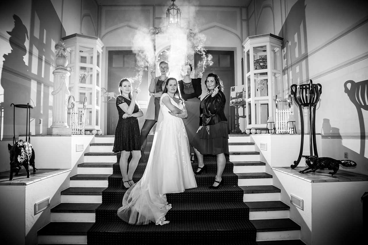 Gruppenfoto Braut steht cool ihren besten Freundinnen auf Treppe im Eingangsbereich Schloss Bredenfelde und alle rauchen - Hochzeitsfotograf Bredenfelde