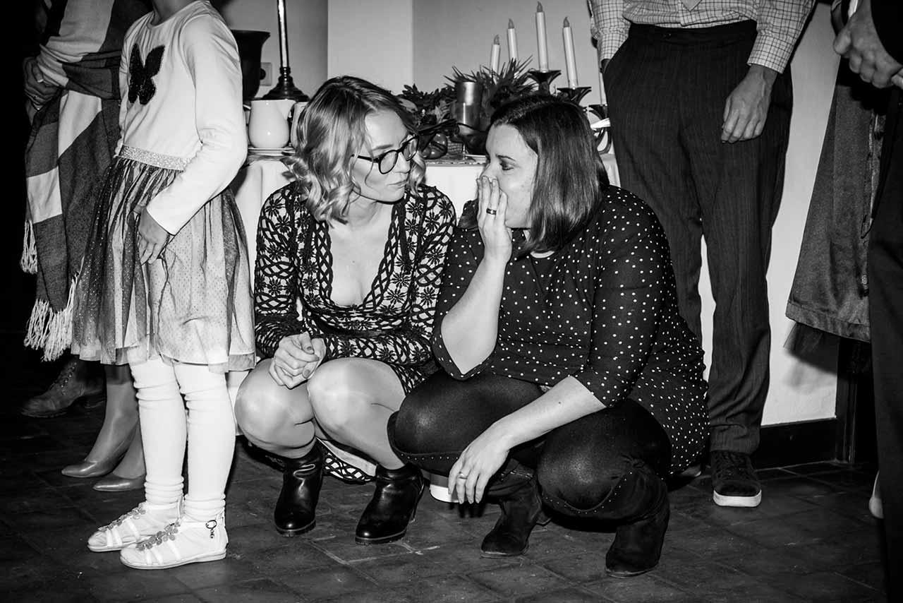 zwei Frauen in der Hocke reden miteinander und schauen erstaunt - Hochzeitsfotograf Rostock