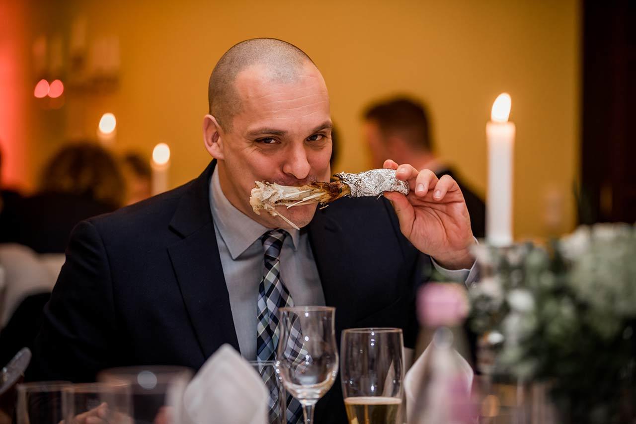 Hochzeitsgast beim Essen mit großer Fleischkeule im Mund - Hochzeitsfotograf Bredenfelde